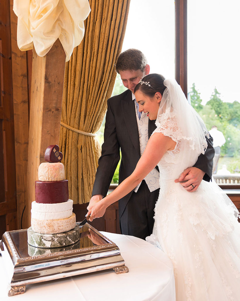 Sarah & Matt cutting into their cheese wedding cake